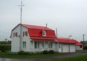 50 km vor Montreal, Provinz Quebec. Oft haben Häuser schrille Farben am Dach. Typischer Stil hier mit Garagen und einem Postkasten vor dem Haus.